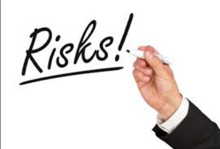 Hand writing the word risks in black
