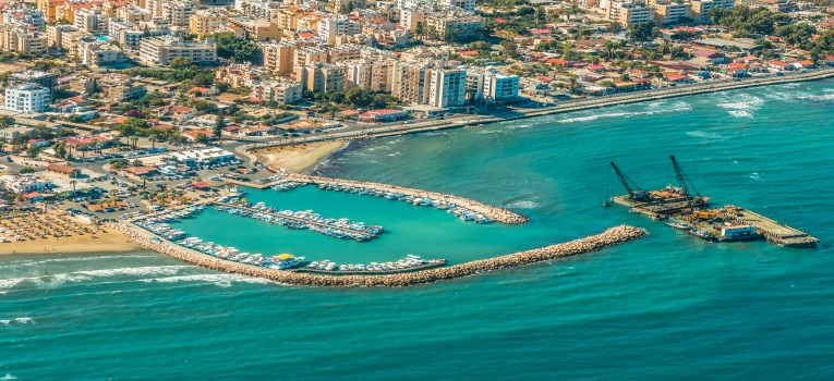 Ariel view of Larnaca Port - blue, green sea with golden sand