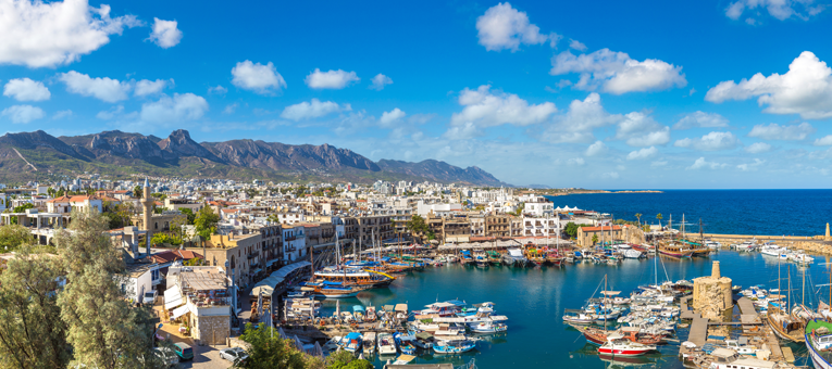 View of harbour in Cyprus with boats in the sea, property and moutains in the background